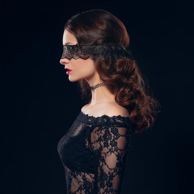 Fille en lingerie masque noir sur fond noir Photo Premium