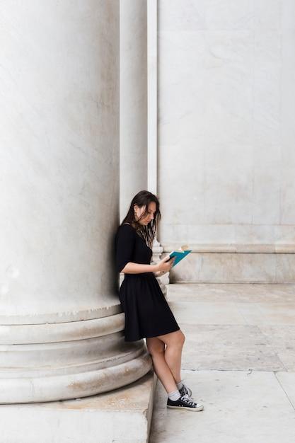 Fille lisant un livre dans la rue Photo gratuit