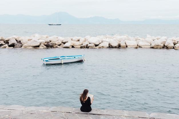 Fille lisant un livre sur le quai Photo gratuit