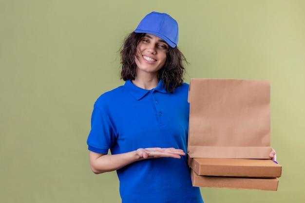Fille De Livraison En Uniforme Bleu Tenant Des Boîtes à Pizza Et Paquet De Papier Présentant Avec Bras De Main Souriant Joyeusement Souriant Sur Vert Isolé Photo gratuit