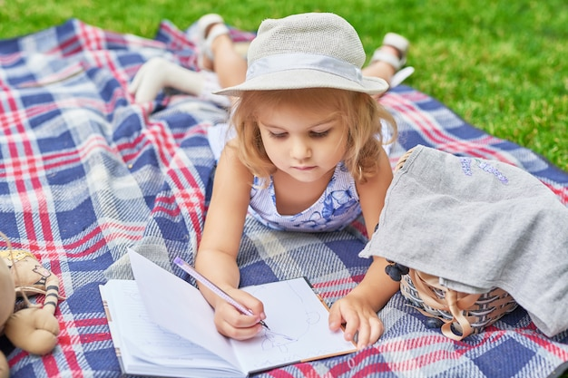 Fille avec un livre dans le parc sur un pique-nique Photo Premium