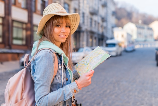 Fille avec look branché tenant la carte de localisation dans la main en regardant la caméra Photo gratuit