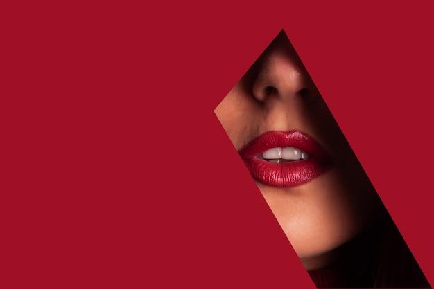Fille avec lumineux maquillage regardant à travers un trou dans le papier Photo Premium