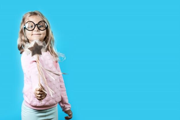 Fille Avec Des Lunettes Et Une Baguette Magique Dit Un Sort Sur Le Bleu Photo Premium