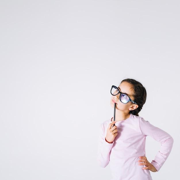Fille à lunettes pensant et levant Photo gratuit