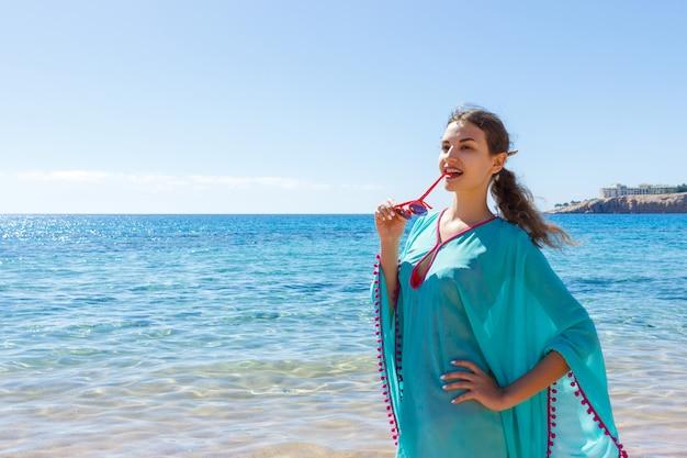 Fille avec des lunettes sur la plage par une journée ensoleillée Photo Premium