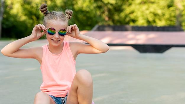 Fille avec des lunettes de soleil assis dans le parc Photo gratuit