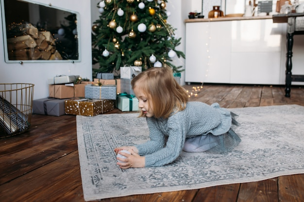 Fille à la maison jouant avec ornement de noël Photo Premium