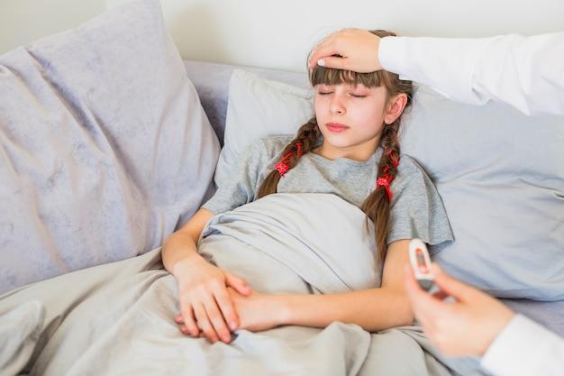 Fille malade en cours d'examen par le médecin Photo gratuit