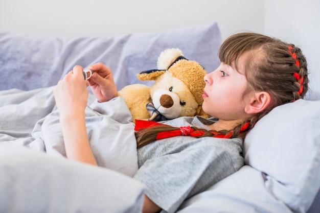 Fille malade utilisant un thermomètre Photo gratuit