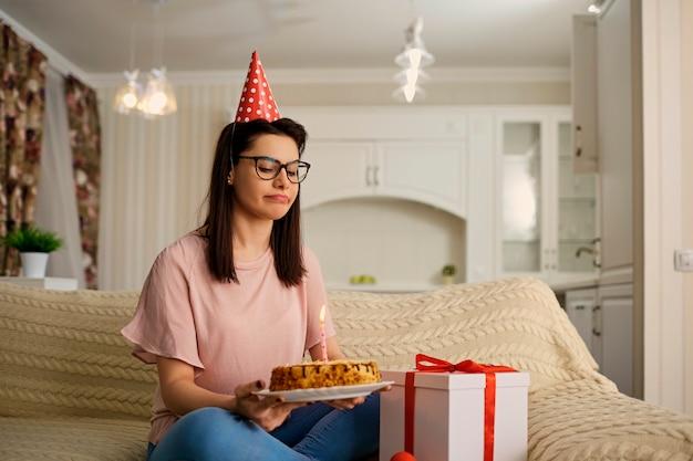 Une fille malheureuse portant un chapeau le jour de son anniversaire avec un gâteau aux chandelles est seule dans la pièce. Photo Premium
