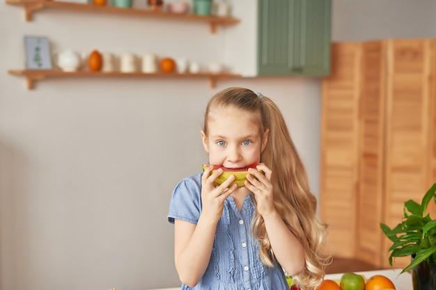 Fille Mange Des Fruits à La Cuisine Photo Premium