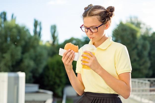 Une Fille Mange Un Sandwich Et Boit Du Jus D'orange Photo Premium