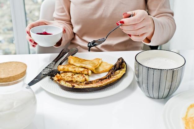 Fille mangeant des crêpes avec de la confiture de myrtilles, petit déjeuner avec café. Photo Premium