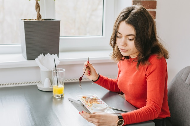 Fille mangeant dans un restaurant Photo gratuit