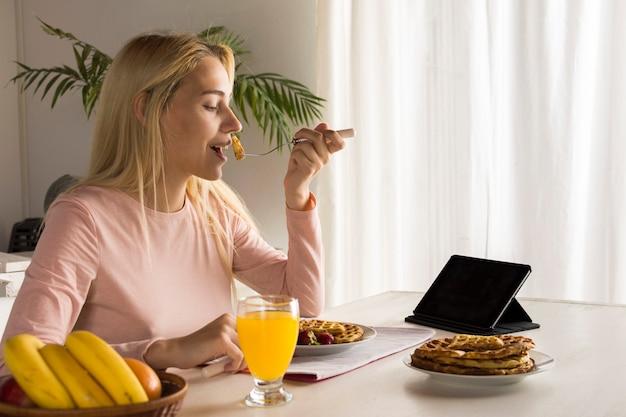 Fille mangeant des gaufres en regardant tablette Photo gratuit