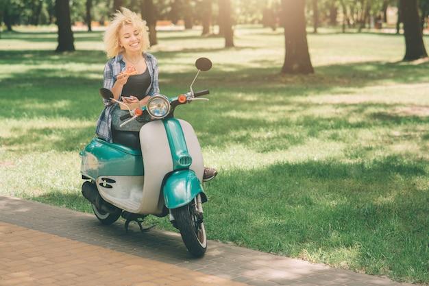 Fille Mangeant Sur Moto Scooter Ou Cyclomoteur. Fille Mangeant Sur Moto Scooter Ou Cyclomoteur. Heureuse Jeune Femme Tenant Une Pizza Chaude Dans La Boîte. Une étudiante N'a Pas Le Temps, Il Va Manger Sur Le Pouce Photo Premium