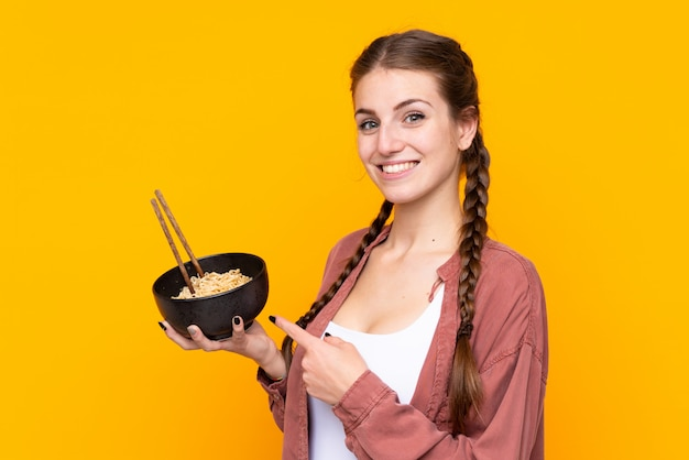 Fille Mangeant Des Nouilles Sur Un Mur Jaune Isolé Photo Premium