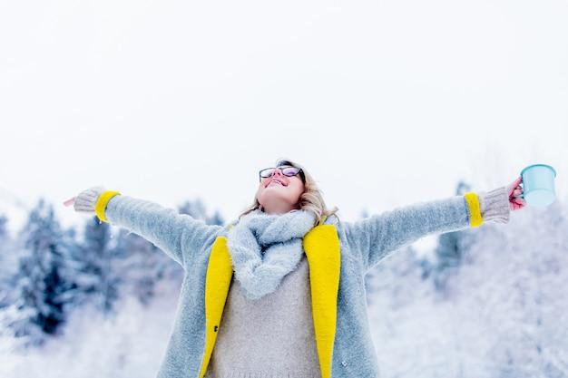 Fille en manteau avec une tasse de boisson dans une forêt de neige Photo Premium