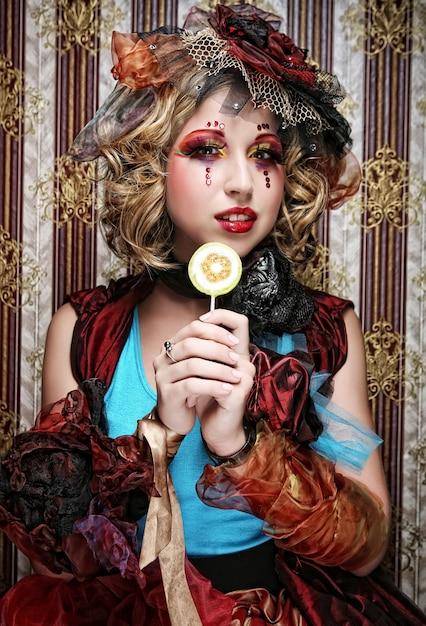 Fille avec maquillage créatif est titulaire de sucette. Photo Premium