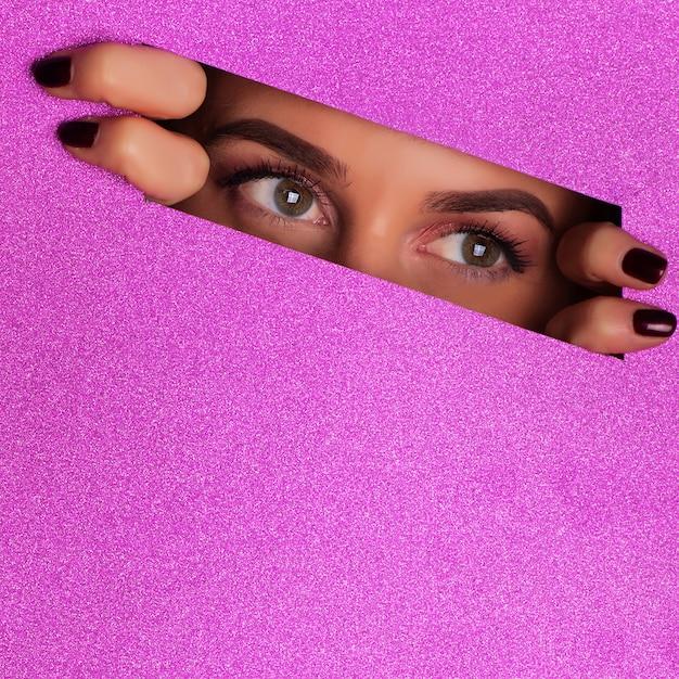 Fille avec un maquillage lumineux à la recherche à travers un trou en papier violet backgroun Photo Premium