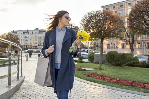 Fille marche dans la ville, jeune femme avec bouquet de fleurs et sac à provisions Photo Premium