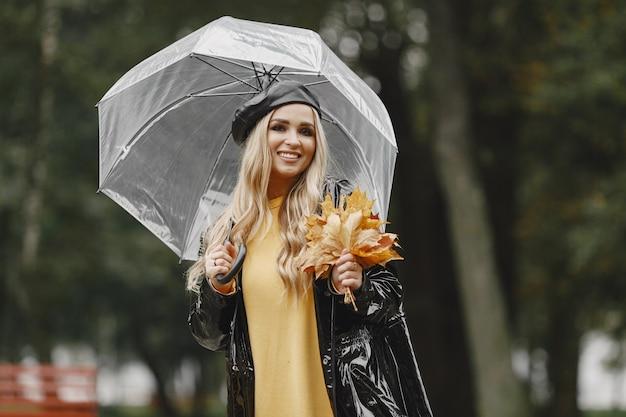 Fille Marche. Femme En Manteau Noir. Blonde Avec Un Bonnet Noir. Dame Au Parapluie. Photo gratuit