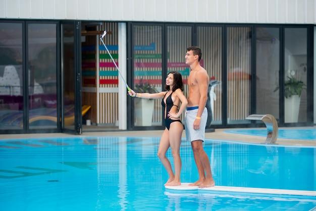 Fille avec mec près de la piscine prenant selfie photo Photo Premium
