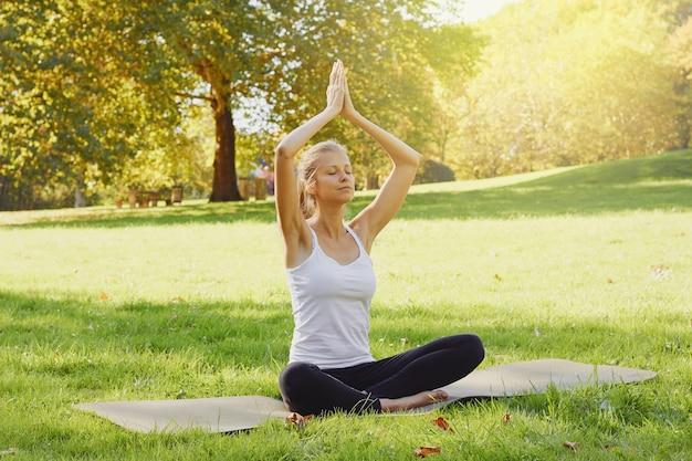 Fille médite tout en pratiquant le yoga en plein air dans le parc Photo Premium