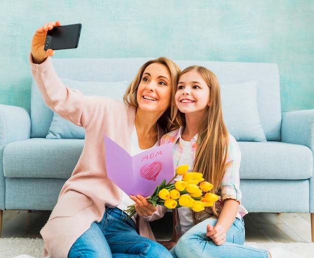 Fille et mère avec des cadeaux prenant selfie Photo gratuit