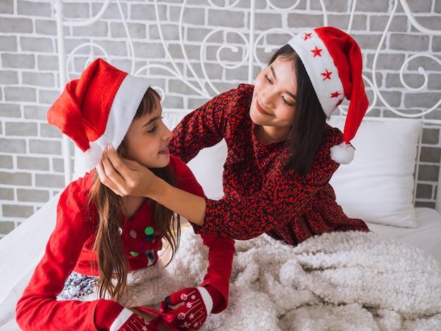 La fille et la mère célèbrent le jour de noël à la maison Photo Premium