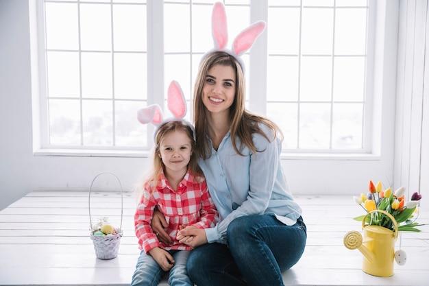 Fille et mère dans les oreilles de lapin assis près de panier avec des oeufs colorés Photo gratuit
