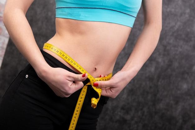 La fille mesure sa taille avec le type de mesure. fermer Photo Premium