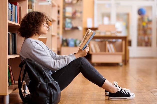 Fille Métisse En Tenue Décontractée Assis Sur Le Sol Par Des étagères Dans La Bibliothèque Du Collège Et Livre De Lecture Photo Premium