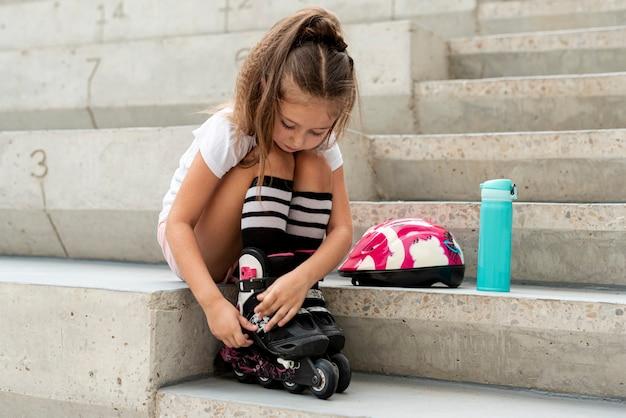 Fille mettant des patins à roues alignées Photo gratuit