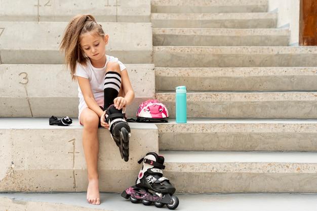 Fille mettant des patins à roulettes noirs Photo gratuit
