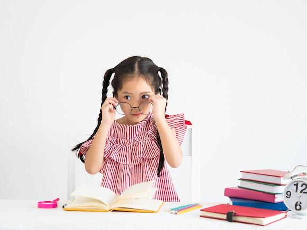 Fille mignonne asiatique avec un livre sur le bureau Photo Premium
