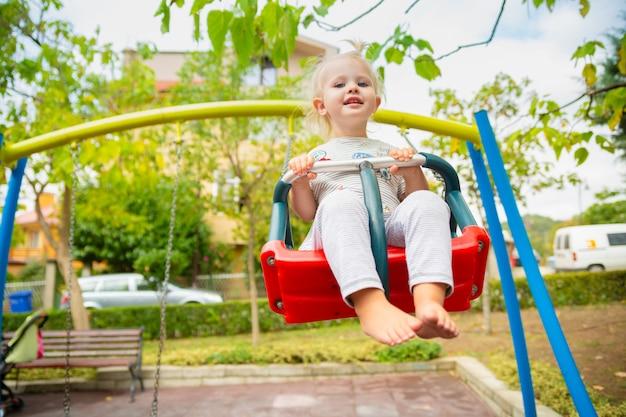 Fille mignonne blanche à cheval sur une balançoire sur le terrain de jeu en été. Photo Premium