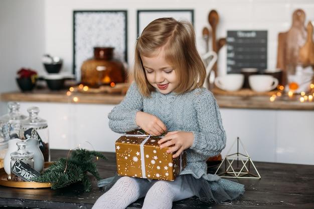 Fille mignonne avec boîte de cadeau de noël dans la cuisine. joyeux noël et joyeuses fêtes! Photo Premium