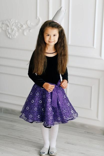 Fille mignonne élégante avec une couronne de jouet blanche dans un chemisier noir et une jupe violette Photo Premium