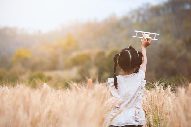 Fille mignonne enfant asiatique en cours d'exécution et jouant avec avion en bois jouet dans le champ d'orge Photo Premium
