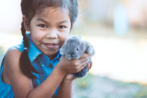 Fille mignonne enfant asiatique jouant avec petit lapin avec amour et tendresse Photo Premium