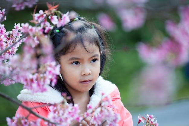 Fille mignonne enfant asiatique profiter avec beau jardin de fleurs de cerisier rose Photo Premium
