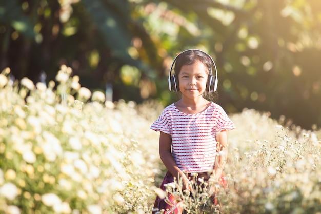 Fille Mignonne Enfant Asiatique S'amuser à écouter De La Musique Au Casque Dans Le Champ De La Fleur Photo Premium