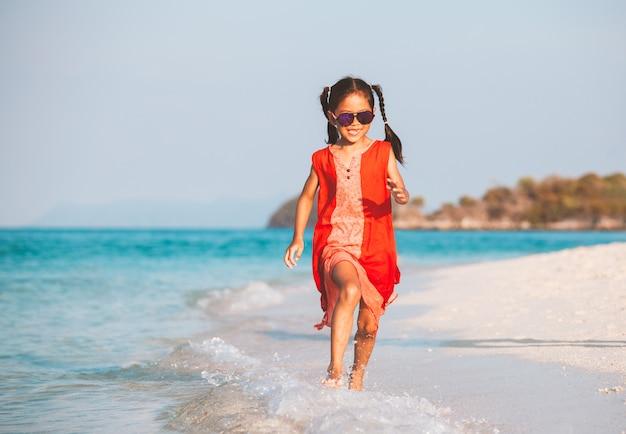Fille mignonne enfant asiatique s'amuser à jouer et courir sur la plage près de la mer magnifique en vacances d'été Photo Premium