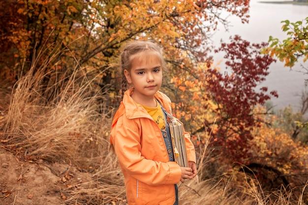 Fille mignonne intelligente tenant un livre avec des feuilles jaunes sèches Photo Premium