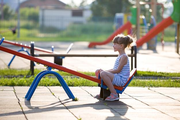 Fille mignonne jeune enfant à l'extérieur sur balançoire en balançoire sur une journée d'été ensoleillée Photo Premium
