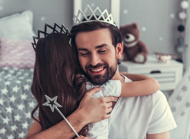 Une Fille Mignonne Et Son Beau Papa En Couronne S'enlacent. Photo Premium