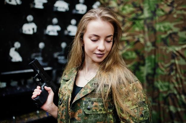 Fille Militaire En Uniforme De Camouflage Avec Un Pistolet à Portée De Main Sur Fond De L'armée Sur Le Champ De Tir. Photo Premium