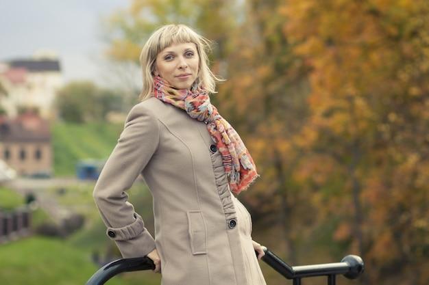 Fille de mode automne portant un trench-coat léger dans un feuillage de flare de soleil Photo Premium